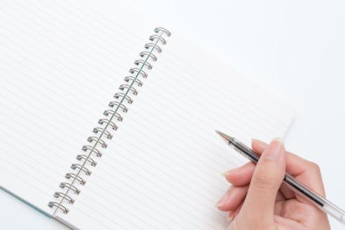 ペンを持つ手とノート