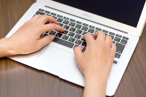 MacBook Airのキーを打つ手